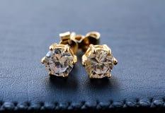 Gold earrings with diamonds. Macro shot Stock Image