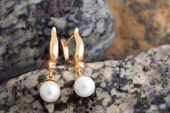Gold Earrings with Diamonds and Pearls on the natural stones bac Royalty Free Stock Images