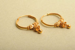 Gold earrings. Fashion jewelry of gold ear rings on mat paper background Royalty Free Stock Image