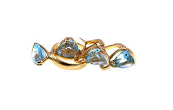 Gold earrings and a ring with a dark blue topaz Stock Photos