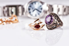 Gold earrings and rings with red rubies and watch Royalty Free Stock Photography
