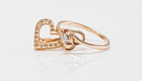 Gold earrings in the shape of a heart and a thin ring with diamo Stock Photography