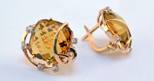 Gold earrings with whiskey quartz and zircons Royalty Free Stock Photo