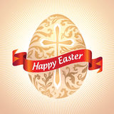 Gold Easter egg with flower pattern over cross and Stock Photos