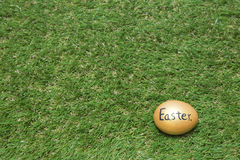 Gold easter egg on green grass Royalty Free Stock Photography