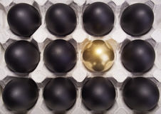Gold Easter egg between many black eggs Royalty Free Stock Images