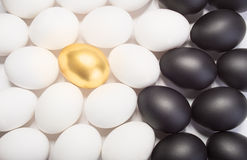Gold Easter egg between many white and black eggs Stock Image