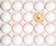 Gold Easter egg between many white eggs Stock Images