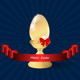 Gold easter egg on a stand with a red bow on a dark background. Royalty Free Stock Image