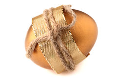 Gold EASTER egg wrapped by golden bow Royalty Free Stock Images