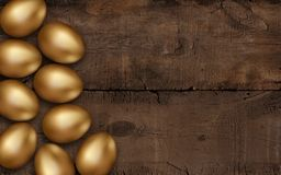 Gold Easter eggs on dark wooden background. Rustic dark background. Colorful golden easter eggs on a wooden table. Invitation