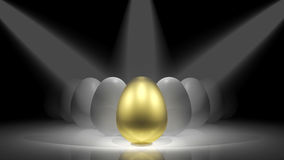 Gold egg. In front of white eggs on the stage Stock Images