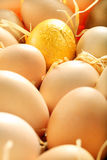Gold egg in a basket full of eggs Stock Photo