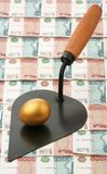 Gold egg and building trowel Stock Photos