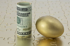 Gold egg and dollar currency on puzzle. Gold egg and rolled, dollar currency placed on shiny golden puzzle in reflection of complex investment and savings Stock Photos