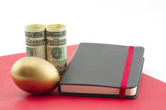 Gold egg, dollars, red folder and journal reflect planned succes Stock Image