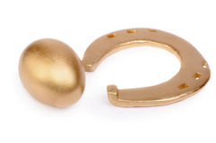 Gold egg and gold horseshoe Stock Photos