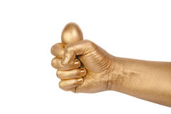 Gold egg in a gold man's hand Royalty Free Stock Photography