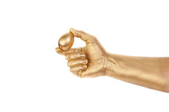 Gold egg in a gold man's hand Stock Image