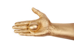 Gold egg in a gold man's hand Stock Photography