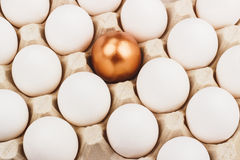 Gold egg between white eggs Royalty Free Stock Photo