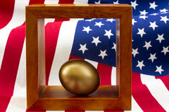 Gold egg in wood frame with stars and stripes flag pattern rippl Royalty Free Stock Photo