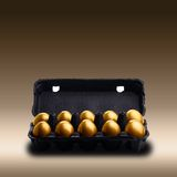 Gold eggs in a black carton Stock Photo