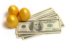 Gold eggs and dollar. Three gold eggs to a heap with money Royalty Free Stock Photo