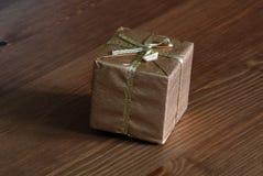 Gold eingewickeltes Geschenk auf Holz Stockfotografie
