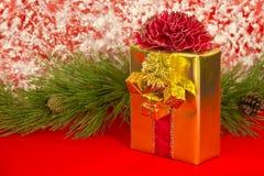 Gold-eingewickeltes Geschenk mit lockigem rotem Bogen Lizenzfreie Stockfotografie