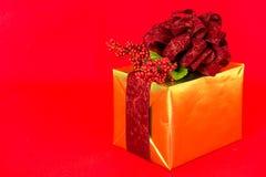 Gold-eingewickeltes Geschenk mit rotem Damast-Farbband. Lizenzfreies Stockbild