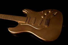 Gold electric guitar on a dark background Royalty Free Stock Image
