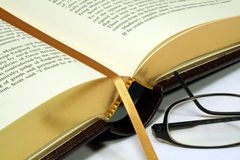 Gold Embossed Book with Reading Glasses. This is a close up image of a gold embossed book with reading glasses royalty free stock photo