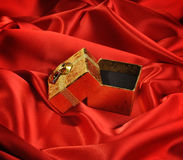Gold empty boxes on red silk Stock Photo