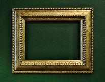 Gold empty picture frame border on green wall. Background royalty free stock photo