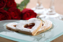 Gold engagement ring and shortbread hearts Royalty Free Stock Photography