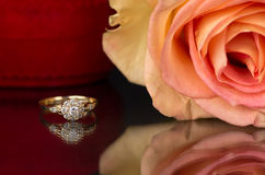 Gold engagement, rose and a box on the mirror background. Royalty Free Stock Image