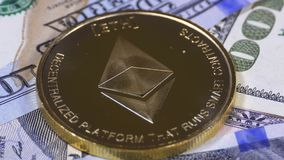 Gold Ethereum Coin, ETH and Bills of Dollars are Rotating. Crypto Currency Close-up. Dollar banknotes of various denominations on which lies the cryptocurrency stock footage