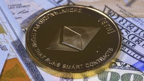 Gold Ethereum Coin, ETH and Bills of Dollars are Rotating. Crypto Currency Close-up. Dollar banknotes of various denominations on which lies the cryptocurrency stock video