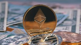 Gold Ethereum Coin, ETH and Bills of Dollars are Rotating. Different Crypto Currency Close-up. Macro. Dollar banknotes of various denominations on which lies stock video