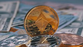 Gold Ethereum Coin, ETH and Bills of Dollars are Rotating. Different Crypto Currency Close-up. Macro. Dollar banknotes of various denominations on which lies stock footage