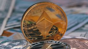 Gold Ethereum Coin, ETH and Bills of Dollars are Rotating. Different Crypto Currency Close-up. Macro. Dollar banknotes of various denominations on which lies stock video footage