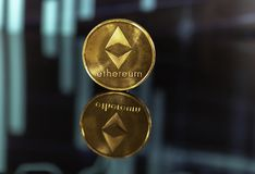 Gold ethereum coin isolated on black background with reflection and stock candles. royalty free stock images