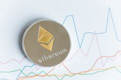 Gold ethereum cryptocurrency coin on rising line graph trading c Stock Photography