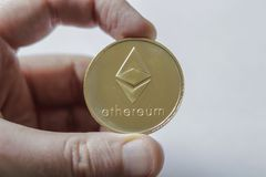 A Large Etherium Token in hand. A gold Etherium token in hand White Background stock image