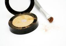 Gold eyeshadow and brush Stock Image