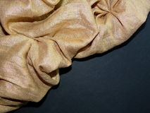The gold fabric on black background Royalty Free Stock Images