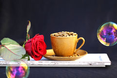 Gold-farbige Kaffeetasse mit Kaffeebohnen Stockbilder