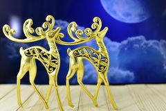 Gold figures of deer in the background of the moon Stock Images