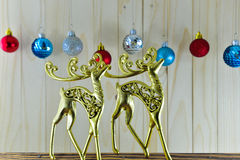 The gold figures of deer and Christmas ornaments on wooden backg Royalty Free Stock Image